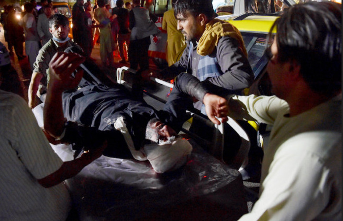 Medical and hospital staff bring an injured man on a stretcher for treatment after two blasts, which killed at least five and wounded a dozen, outside the airport in Kabul on August 26, 2021.